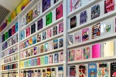 Den färgrika iPhonen och Samsung ringer fall som är till salu i mobiltelefondiversehandel arkivbilder