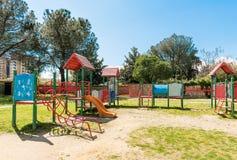 Den färgrika lekplatsen för ungar inom ett stads- offentligt parkerar, Italien Arkivfoto