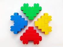 Den färgrika leksaken blockerar hjärtor på vit bakgrund arkivbilder
