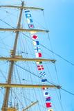 Den färgrika nautiska seglingen sjunker flyg i vinden från linjerna av en segelbåtmast backlit i ljus blå himmel av solen arkivbilder