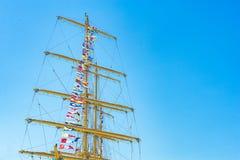 Den färgrika nautiska seglingen sjunker flyg i vinden från linjerna av en segelbåtmast backlit i ljus blå himmel av solen royaltyfria bilder