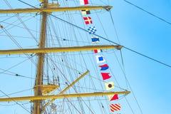 Den färgrika nautiska seglingen sjunker flyg i vinden från linjerna av en segelbåtmast backlit i ljus blå himmel av solen royaltyfri foto