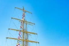 Den färgrika nautiska seglingen sjunker flyg i vinden från linjerna av en segelbåtmast backlit i ljus blå himmel av solen royaltyfri bild