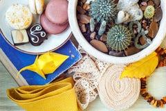 Den färgrika pappers- origamin, kulöra makron, tappning snör åt bandet, bärnsten, blomman i en kruka, boken och servetten på tabe royaltyfri bild