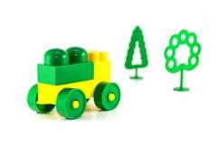 Den färgrika plast- leksaken blockerar bilen och träd Royaltyfri Foto