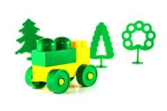 Den färgrika plast- leksaken blockerar bilen och träd Arkivbild