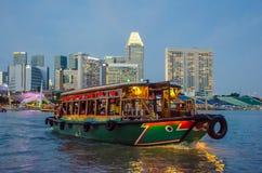 Den färgrika riverboaten kryssar omkring i hamnen på solnedgången med stadshorisonten i bakgrunden Arkivfoto