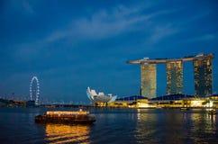 Den färgrika riverboaten kryssar omkring i hamnen på solnedgången med stadshorisonten i bakgrunden Arkivbilder