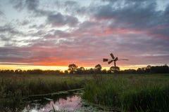 Den färgrika solnedgången med gammalt pumpa maler i bygden av Holland arkivfoto