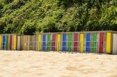 Den färgrika stranden förlägga i barack i rad - horisontal Arkivbild