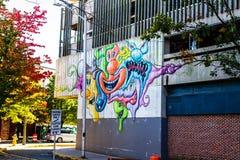 Den färgrika tecknade filmen vänder mot gatakonst på sida av byggnad royaltyfri bild