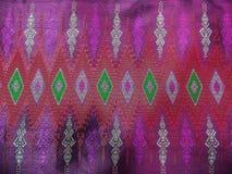 Den färgrika traditionella thailändska purpurfärgade siden- textilmodellen Handcraft texturtappningstil Royaltyfria Bilder