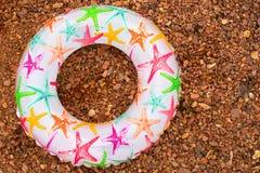 Den färgrika uppblåsbar behandla som ett barn cirkellögner på kusten royaltyfria bilder