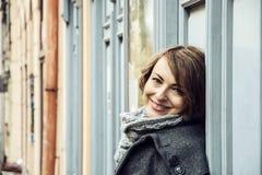 Den förälskade unga caucasian kvinnan lutar på den retro väggen Royaltyfria Foton