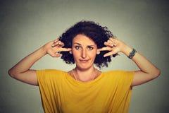 Den förargade ilskna kvinnan som pluggar henne öron med fingrar, önskar inte att lyssna Royaltyfri Fotografi