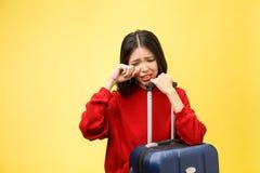 Den förargade turist- kvinnan i tillfällig kläder för sommar sitter på resväskan satte händer på huvudet på gul orange bakgrund royaltyfri bild