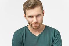 Den förbryllade mannen håller kanter tryckte på, har frustrerat ansiktsuttryck, rynkar pannan framsidan i missnöje och att vara d royaltyfri fotografi