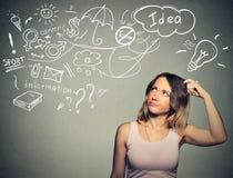 Den förbryllade unga kvinnan som tänker skrapa huvudet, har många idéer som ser upp Arkivfoton