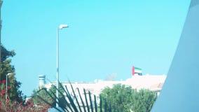 Den Förenade Arabemiraten flaggan som vinkar ovanför ett hus på en tidig klar morgon arkivfilmer