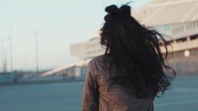 Den förföriska unga kvinnan med naturlig makeup spelar med hennes hår, charmingly leenden och fortsätter att gå joyful mood stock video