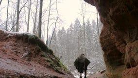Den förhistoriska grottmänniskan går utanför från hans grotta på en bakgrund av vinterskogen stock video
