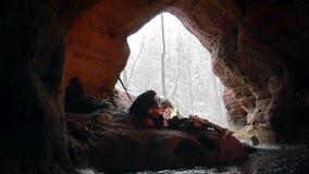 Den förhistoriska grottmänniskan trycker på insnöade tider av stenåldern på bakgrund av vinterskogen lager videofilmer