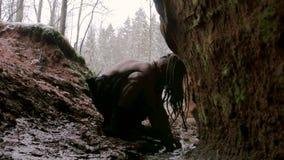 Den förhistoriska grottmänniskan tvättar sig i hans grotta på en bakgrund av vinterskogen stock video