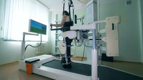 Den förlamad i båda benen patienten öva att gå på en special simulator Virtuell verklighetsimulator för tålmodig rehab stock video