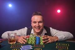 Den förmögna mannen poserar på en pokertabell med chiper och ett exponeringsglas av whisky på det på en kasino royaltyfri bild