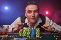 Den förmögna mannen poserar på en pokertabell med chiper och ett exponeringsglas av whisky på det på en kasino royaltyfri fotografi