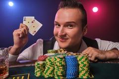 Den förmögna mannen poserar på en pokertabell med chiper och ett exponeringsglas av whisky på det på en kasino arkivfoto