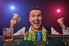 Den förmögna mannen poserar på en pokertabell med chiper och ett exponeringsglas av whisky på det på en kasino royaltyfria foton