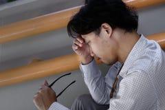 Den försökta stressade unga asiatiska affärsmannen tar av exponeringsglas honom som känner sig uppriven eller besviken med jobb royaltyfri foto