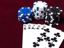Den församlade kombinationen av spolning i poker på den röda torkduken med chiper av olikt värde royaltyfri foto