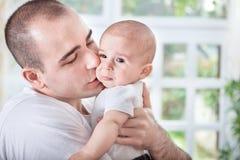 Den försiktiga barnfadern som tröstar att gråta, behandla som ett barn Arkivfoto