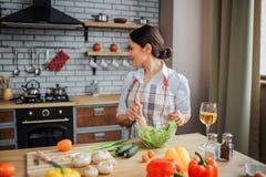 Den försiktiga brunettkvinnan sitter på tabellen och kock i kök Hon blandar sallad i bunke och ser tillbaka på ugnen Alla grönsak arkivfoto