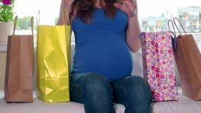 Den försiktiga gravida kvinnan smeker hennes stora mage, når han har shoppat lager videofilmer