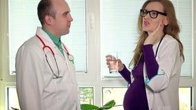 Den försiktiga mandoktorn kommer med exponeringsglas av vatten för hans gravida kollegakvinna på arbete stock video