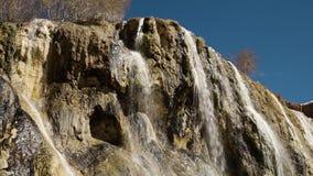 Den försiktiga vattenfallet på den håliga travertinen vaggar kanten arkivfilmer