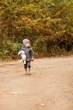 den förskräckta borttappade pojken som går och ser folk i skogen i ett grått lag med en leksak, oavbrutet tjata och plocka svamp  Royaltyfri Fotografi