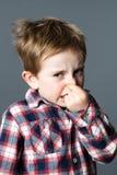 Den förskräckta unga ungen som klämmer hans näsa, förargade vid dålig lukt Royaltyfria Foton