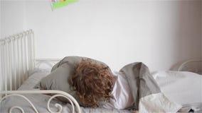 Den försova sig pojken önskar inte att vakna upp, barnnedgångar ut ur säng