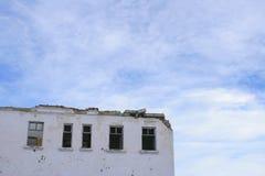 Den förstörda byggnaden på en bakgrund av fridsam himmel Arkivfoton