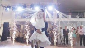 Den första dansen av de härliga lyckliga bröllopparen i den lyxiga restaurangkorridoren dekorerade med brinnande fyrverkerier arkivfilmer