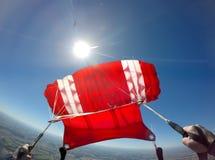 Den första personsikten av ett rött hoppa fallskärm arkivfoto