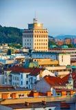 Den första skyskrapan i Ljubljana mellan tak av gamla hus Royaltyfri Bild