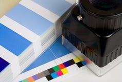 Den förstorande öglan med en press täcker och färgar provkartaboken som bakgrund Royaltyfri Fotografi