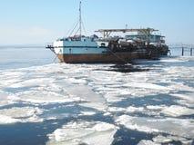 Den förtöjde enorma pråm som laddades med fartyg och fartygställningar på kusten av floden smältte precis, på våren royaltyfri foto