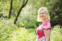den förtjusande blonda skogsommaren går kvinnan Arkivfoto