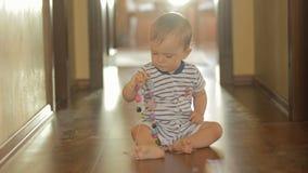 Den förtjusande blondinen behandla som ett barn pojkesammanträde på golv och att spela med färgrika leksaker stock video